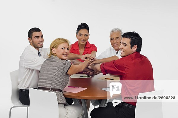 Three businessmen and two businesswomen stacking hands on top of each other in a meeting