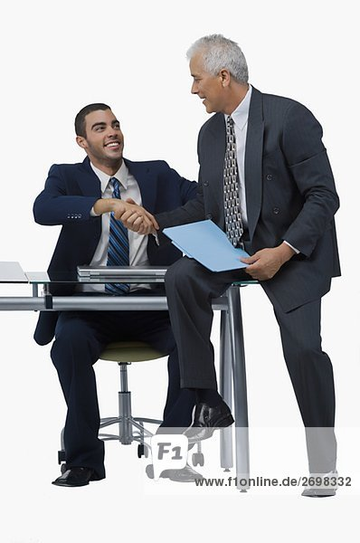 Two businessmen shaking hands and looking at each other