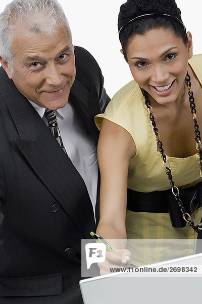 Portrait of a businesswoman and a businessman discussing on a laptop in an office and smiling