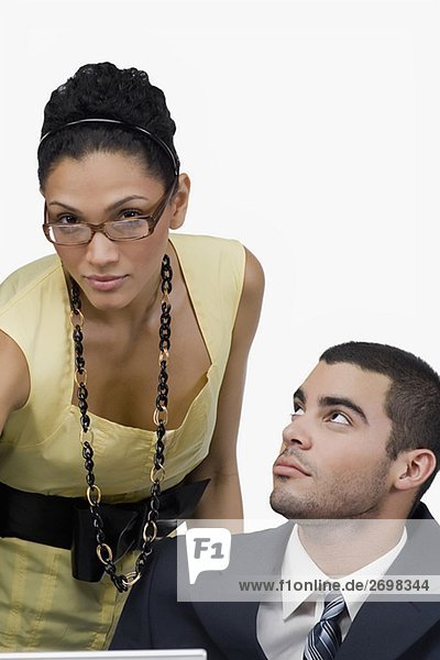 Close-up of a businesswoman with a businessman looking at her in an office