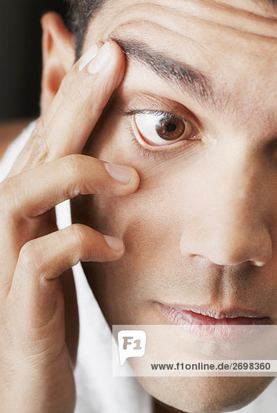 Nahaufnahme eines jungen Mannes Überprüfung sein Auge