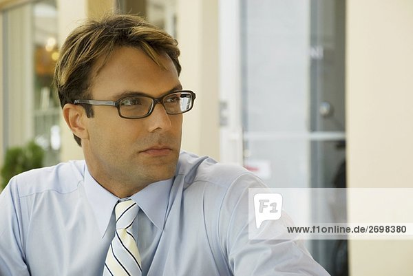 Close-up of a businessman wearing eyeglasses and thinking