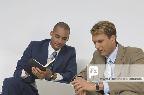Two businessmen looking at a laptop and having a discussion