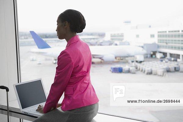 Seitenprofil des mit einem Laptop auf einem Flughafen geschäftsfrau