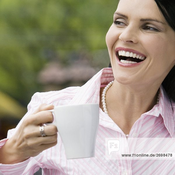 Close-up of a mid adult woman holding a cup of coffee and laughing