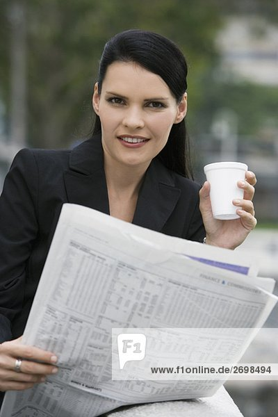 Portrait of a businesswoman holding a disposable cup and a newspaper