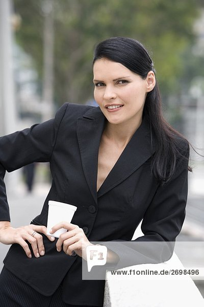 Portrait of a businesswoman holding a disposable cup and smiling