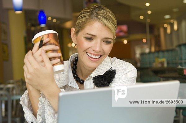 Geschäftsfrau Blick auf einem Laptop und hält einen Pappbecher in einem restaurant