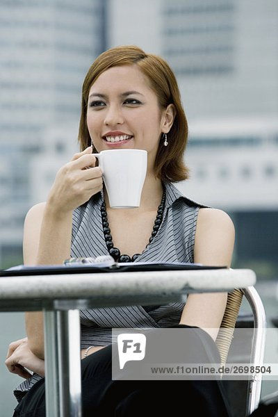Close-up of a businesswoman drinking coffee at a sidewalk cafe