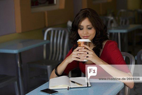 junge Frau hält eine Tasse kaltes Getränk in einem Café