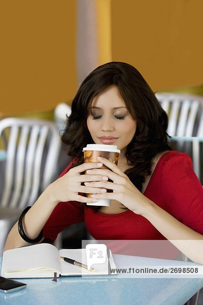 Young woman holding a cup of cold drink in a cafe