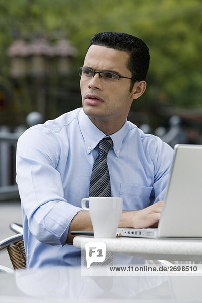 Close-up of a businessman thinking while using a laptop