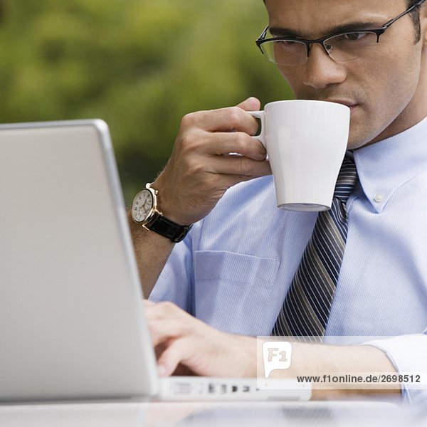 Close-up of a businessman drinking coffee while using a laptop