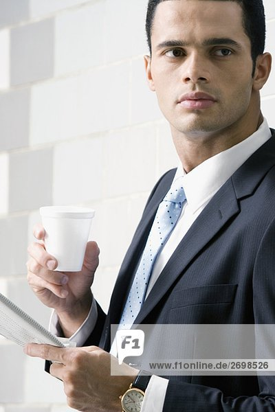 Side profile of a businessman holding a newspaper and a disposable cup