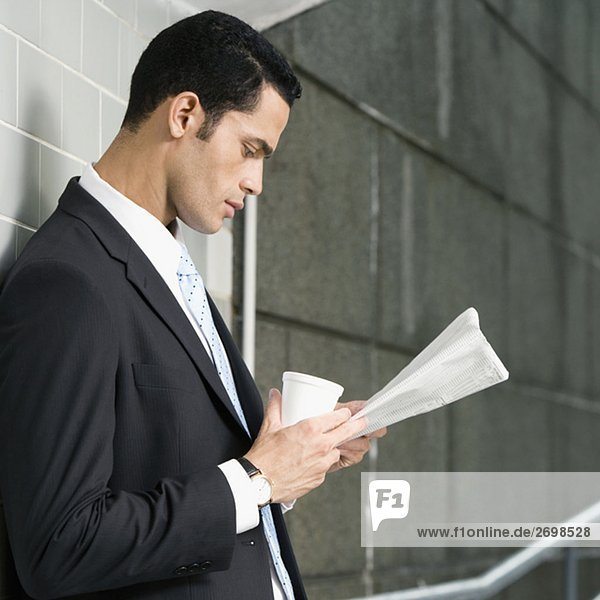 Side profile of a businessman reading a newspaper