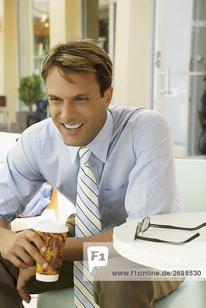 Kaufmann sitzen in einem Restaurant und hält einen Pappbecher