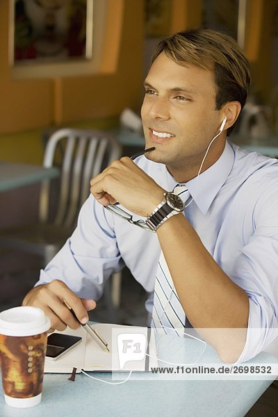 Businessman listening to an MP3 player and smiling