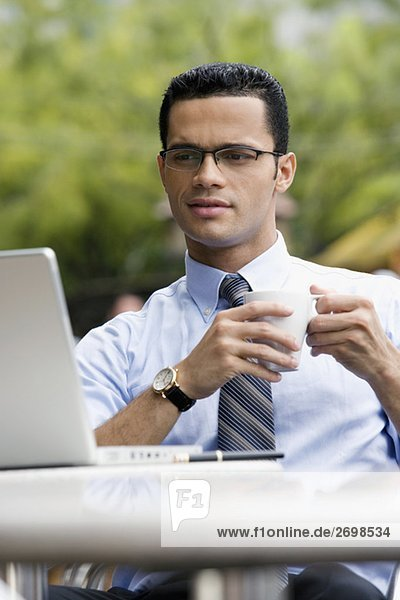 Businessman holding a cup of coffee and looking at a laptop