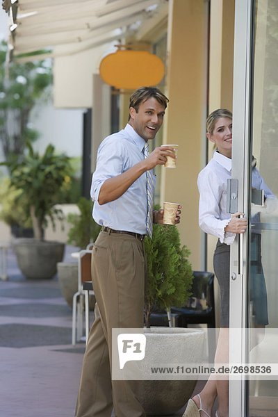 Portrait of a businessman holding two cups of coffee and standing near a businesswoman
