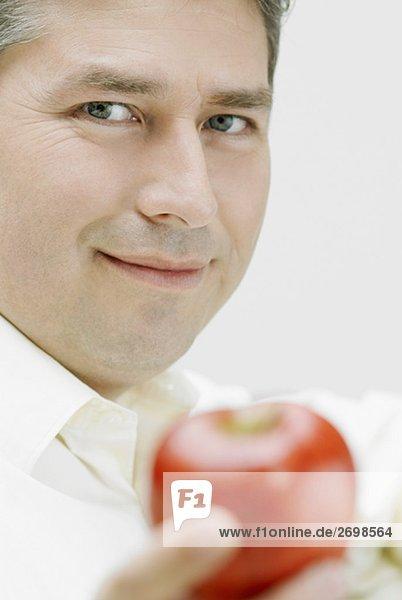Porträt von ein älterer Mann hält einen Apfel
