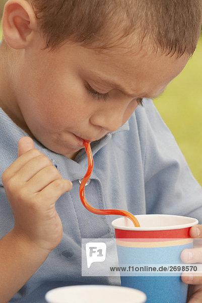 Nahaufnahme eines jungen aus einer Tasse mit einem Strohhalm trinken