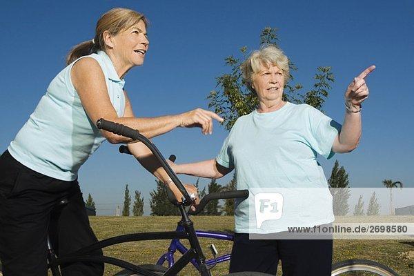 stehend Senior Senioren Frau zeigen 2 Fahrrad Rad