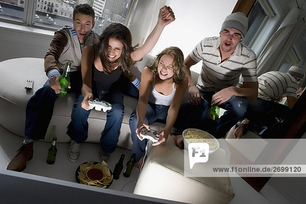 Two young couples playing video game and smiling