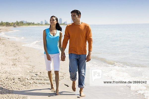 Junge Frau und ein Mitte Erwachsenen Mann zu Fuß am Strand