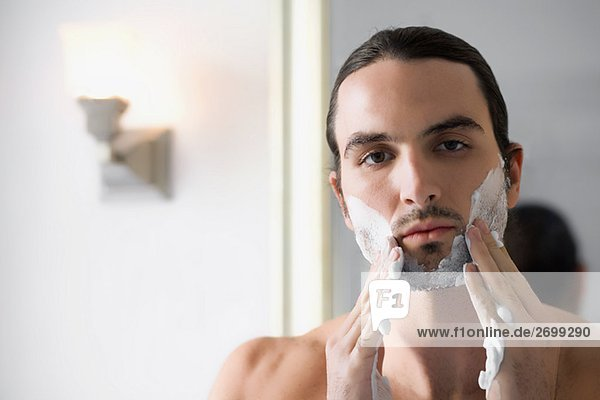 Close-up of a young man applying shaving cream on his face