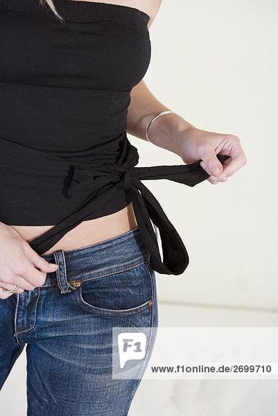 Mitte Schnittansicht einer jungen Frau binden einen Knoten auf ihr top