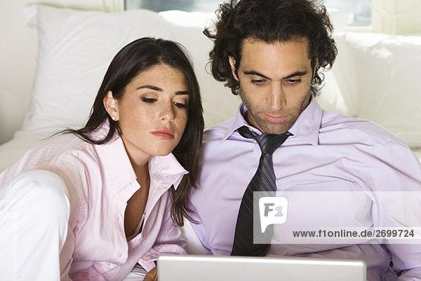 Nahaufnahme eines Kaufmanns und sitzen auf dem Bett mit einem Laptop geschäftsfrau