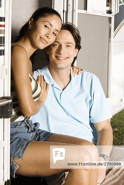 Portrait of a young woman sitting with her arm around a mid adult man