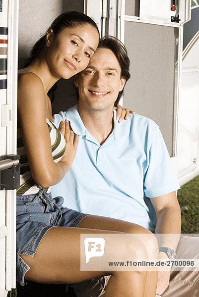 Portrait einer jungen Frau mit ihrem Arm um einen Erwachsenen Mann Mitte sitzend