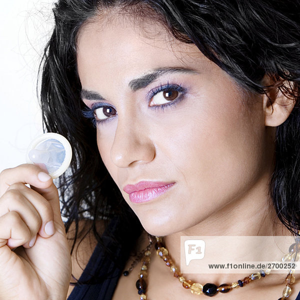 Portrait of a young woman holding a condom