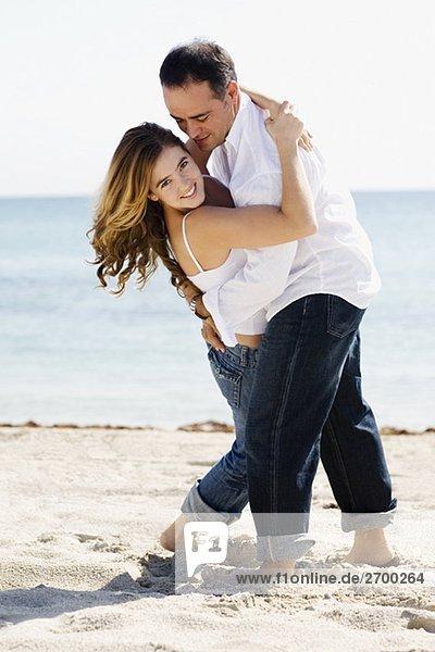 Mitte erwachsenen Menschen umarmen eine junge Frau am Strand