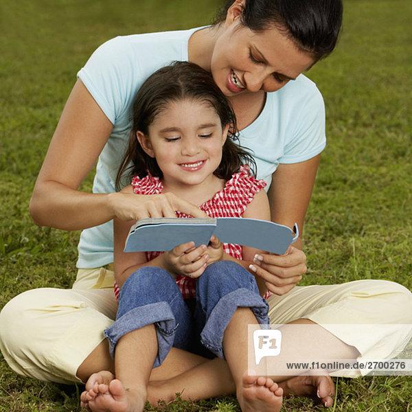 Mädchen sitzen auf der Mutter Schoß und ein Buch zu lesen