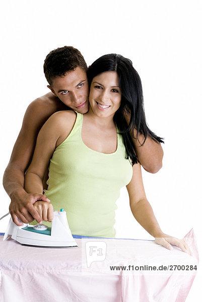Junge Frau mit einem jungen Mann umarmen sie von hinten Bügeln