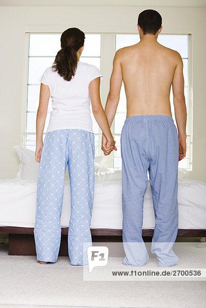 Rückansicht eines jungen Paares Hände