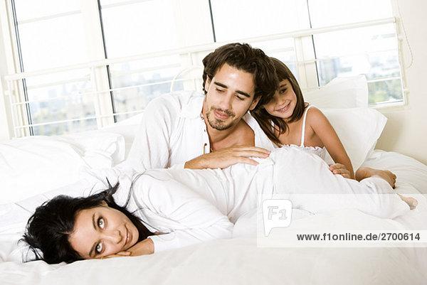 Eltern und ihre Tochter auf dem Bett