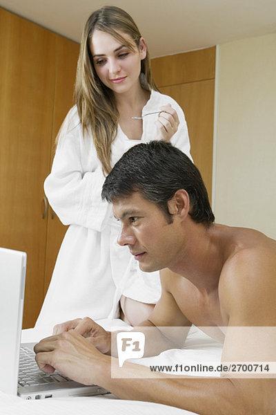 Seitenansicht eines Mitte Erwachsenen Mannes mit einem Laptop mit einer jungen Frau neben ihm stehen