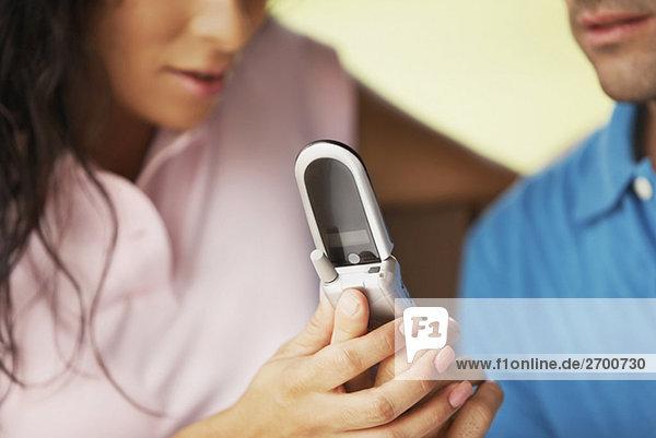 Junger Mann und eine junge Frau mit einem Mobiltelefon