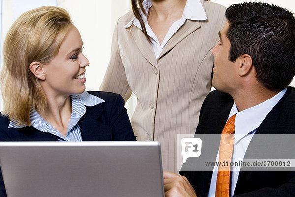 Nahaufnahme eines Kaufmanns und zwei gespann Gespräch an einen laptop