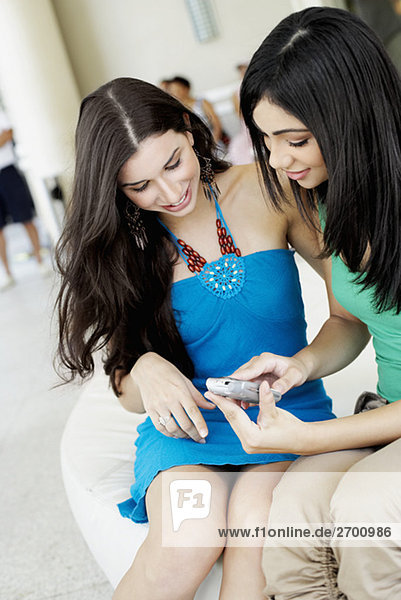 Close-up of a young woman and a teenage girl looking at a mobile phone