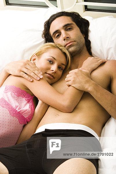 Porträt eines jungen Paares auf dem Bett liegend