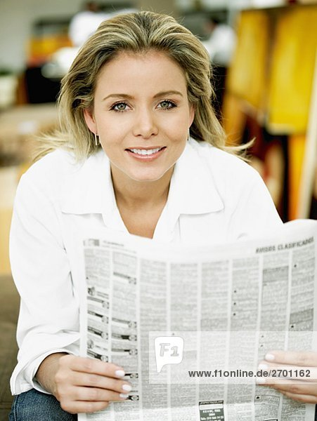 Portrait einer Mitte erwachsen frau hält eine Zeitung und lächelnd