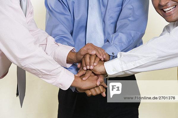Nahaufnahme der drei Geschäftsmänner Händeschütteln