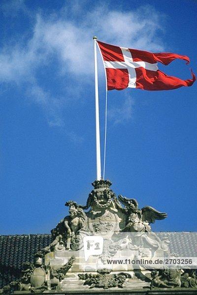 Dänische Flagge flattern auf eine Skulptur  Amalienborg Palast  Kopenhagen  Dänemark