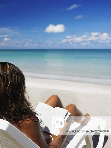 Frau auf einer Chaiselounge sitzen und lesen ein Buch über den Strand  Providencia  Providencia y Santa Catalina  Departamento San Andres y Providencia  Kolumbien