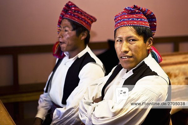 Close-up of two young men taking part in a wedding ceremony  Taquile Island  Lake Titicaca  Puno  Peru