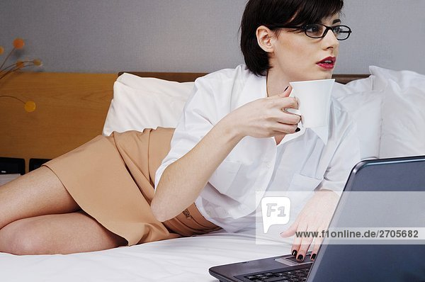 Businesswoman working on a laptop and having tea